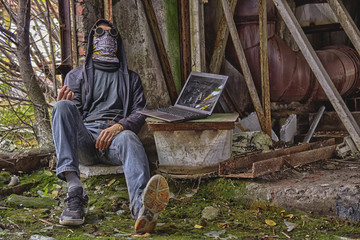 Cyber punk or fantastic or postapocalyptic or future world man cosplayer in goggles, skull mask and hood (cyber junkie with wire from hand to laptop), inside of rusty destructed radioactive  factory