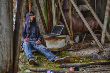 Cyber punk or fantastic or postapocalyptic or future world man in goggles and hood (cyber junkie with wire from hand to laptop), inside of destructed mossy radioactive  factory. Audio or cyber drugs
