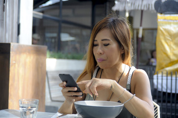 beautiful and happy Asian woman using mobile phone texting on internet social media smiling relaxed