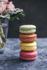 Stack of colorful macarons on grey background