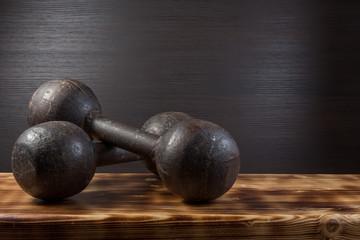 Old dumbbells on wood surface. Dark background.