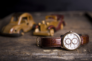Closeup toned shot of male watches lying on table against  retro set