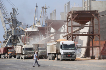 Man walks past a cargo ship unloading wheat at the Red Sea port of Hodeida, Yemen