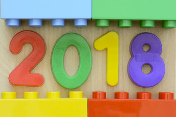Close up of year 2018 in colorful plastic numbers surrounded by plastic toy blocks
