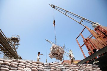 Workers stand as a cargo ship unloads sugar at the Red Sea port of Salif, Yemen