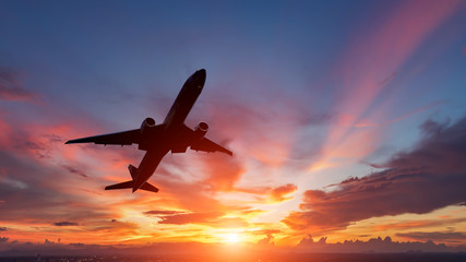 The silhouette of a passenger plane flying in sunset. Wall mural