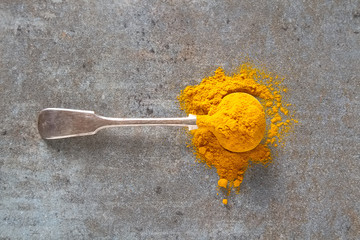 Turmeric powder and fresh turmeric. Dark background. Space for text.