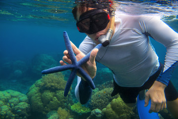 Man snorkeling in blue water with star fish. Snorkeling in coral reef. Snorkel holds blue starfish.