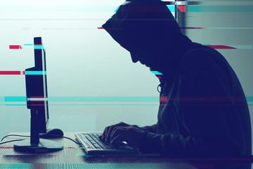 Hooded computer hacker working on desktop PC computer