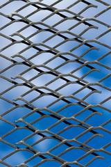 Metallgitter vor blau-weißem Himmel