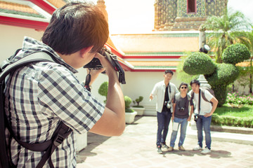 Male tourist holding a camera and taking pictures friends.