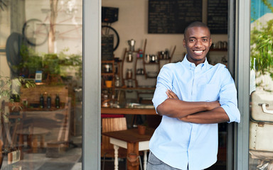Smiling African entrepreneur standing at the door of his cafe