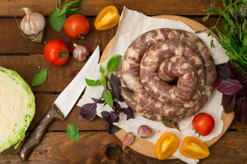 Raw fresh sausages in a white plate on a wooden background. Top view. Close-up