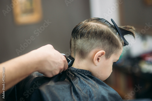 Little Boy Getting Haircut By Barber While Sitting In Chair At Barbershop