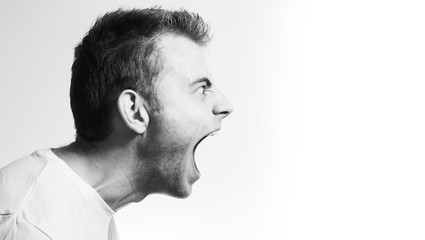 screaming angry aggressive militant man profile on a white background, black and white portrait, evil