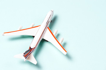 White toy plane on light blue background. Top view