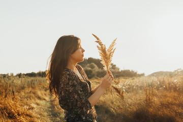 Young boho woman in meadow field
