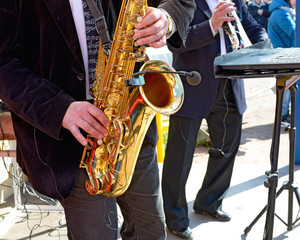 The saxophone in the hands of the musician.