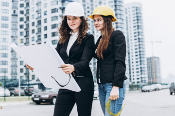 Two business women in protective helmets and safety glasses looking at building schemes, architectural concept