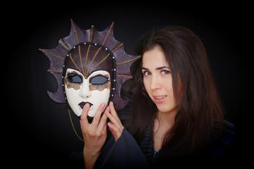 brunette girl holds a carnival mask