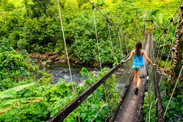 Young woman walking on suspension bridge over Wainibau stream, Lavena Coastal Walk, Taveuni Island, Fiji