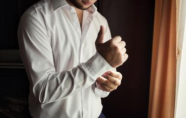 Businessman dress shirt. The man in the white shirt in the window dress cufflinks. Politician, man's style, Businessman buttoning his shirt,male hands closeup, American, European businessman