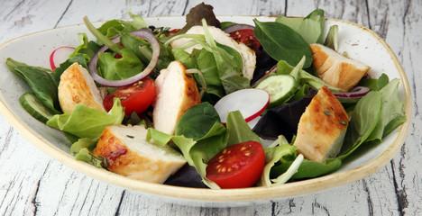Chicken salad with leaf vegetables and cherry tomatoes.