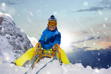 Kind auf dem Schlitten in den Alpen
