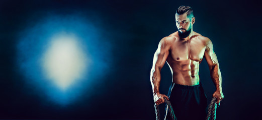 Muscular bearded bodybuilder man Posing with ropein studio.