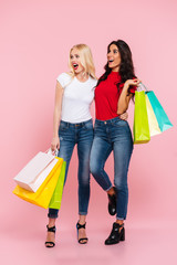 Full length image of two shocked happy women with packages
