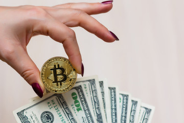 Golden bitcoin coin on women's hand on blurred us dollar bills background copy space