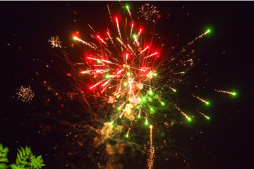 A photo of a salute in the night sky. Bright texture of festive fireworks. Abstract holiday background with various colors fireworks light. New Year's, Christmas lights in the sky, colorful lights.
