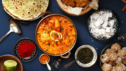Indian cuisine on diwali holiday: tikka masala, samosa, patties and sweets with mint chutney and spices. Dark blue background. Banner composition