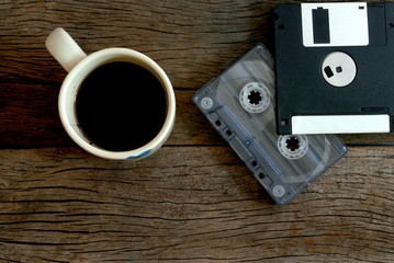 cup of coffee  cassette tape and floppy disk over wooden floor
