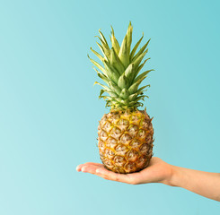 Hand holding a pineapple. Creative layout made of pineapple. Flat lay. Food concept.