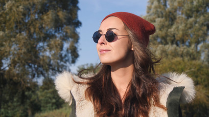 Young pretty hipster mixed race woman in sunglasses smiling and having fun outdoor in sunny day, wearing casual clothes hat and sunglasses