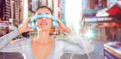 Composite image of smiling woman using virtual video glasses