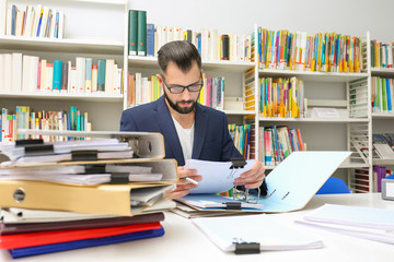 Man working with documents at table in archive