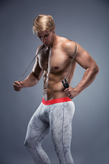 Muscular bodybuilder guy doing exercises with jump rope