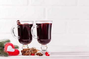 Winter horizontal mulled wine banner. Glasses with hot red wine and spices, tree, felt decorations on wooden background.
