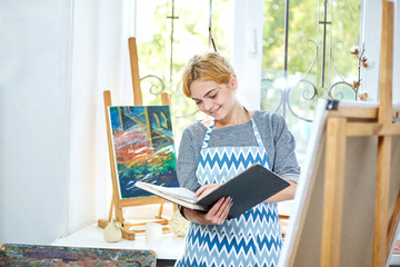 Pretty blode girl looking on a album and smiling. Art concept,