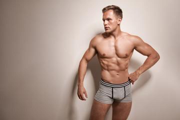 Muscular man in underwear on light background