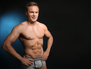 Muscular man in underwear on dark background