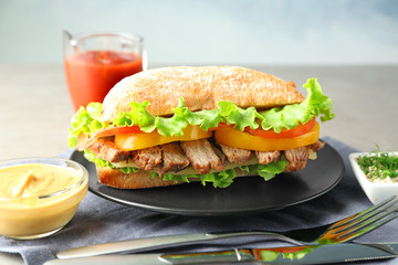 Plate with steak sandwich on table