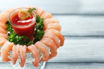 Bowl with shrimp cocktail and tomato sauce on wooden table, closeup
