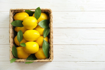 Wicker basket with fresh lemons on wooden table