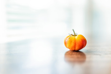 Macro closeup of one small heirloom tiny red or orange tomato on table by window with reflection