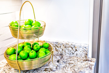Macro closeup of golden tray with bowls of whole fake limes in kitchen in staging model house or apartment