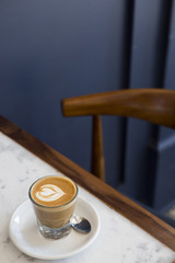 Cortado coffee on table with blue wall in background