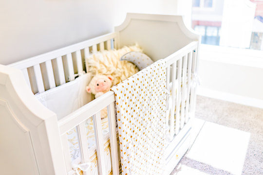 Closeup of bright yellow baby crib in nursery room with toys and pillow in model staging home, apartment or house